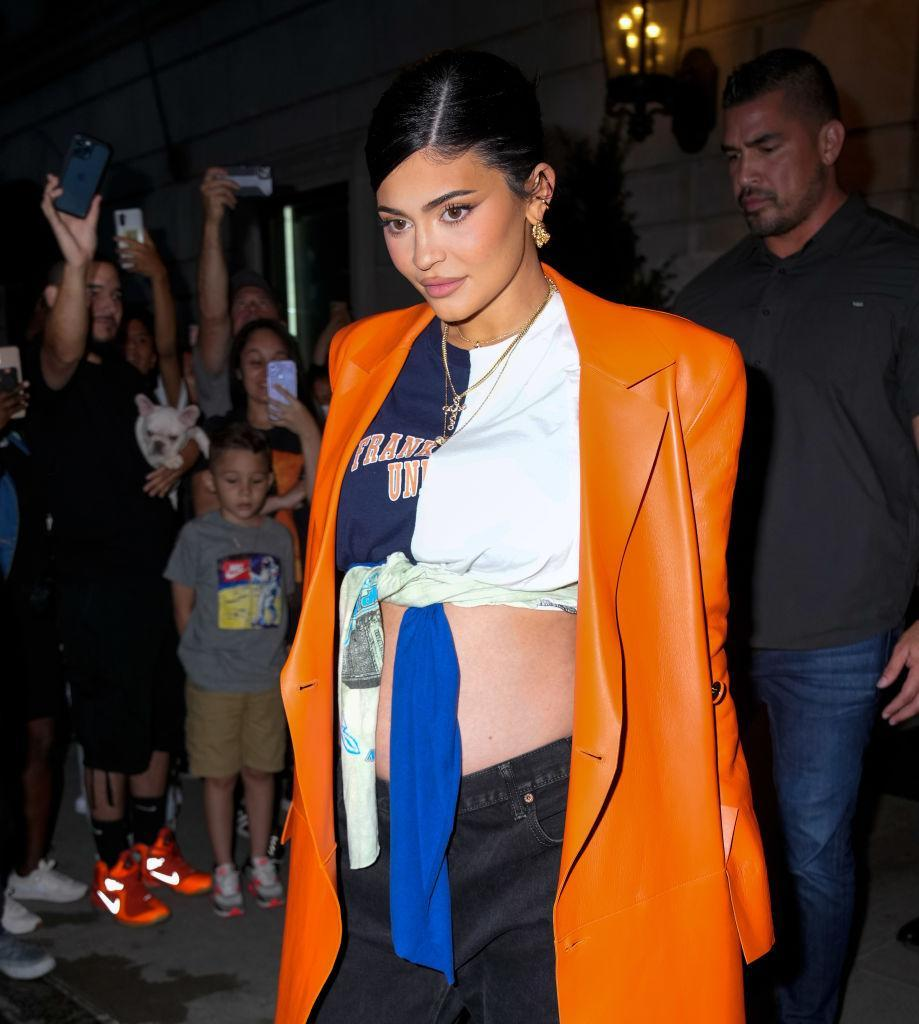 Kylie Jenner frames her bump in a tie-up crop top and orange coat, pictured on September 9, 2021. (Getty Images)