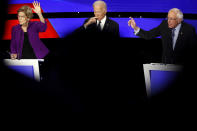Democratic presidential candidate Sen. Elizabeth Warren, D-Mass., and Sen. Bernie Sanders, I-Vt., raise their hands to answer a question as Joe Biden pauses Tuesday, Jan. 14, 2020, during a Democratic presidential primary debate hosted by CNN and the Des Moines Register in Des Moines, Iowa. (AP Photo/Patrick Semansky)
