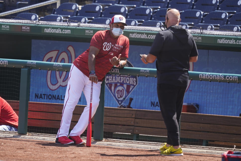 CORRECTS FIRST NAME TO MIKE-Washington Nationals manager Dave Martinez, left, and general manager Mike Rizzo talk during a baseball workout at Nationals Park, Monday, April 5, 2021, in Washington. The Nationals are scheduled to play the Braves on Tuesday. (AP Photo/Alex Brandon)