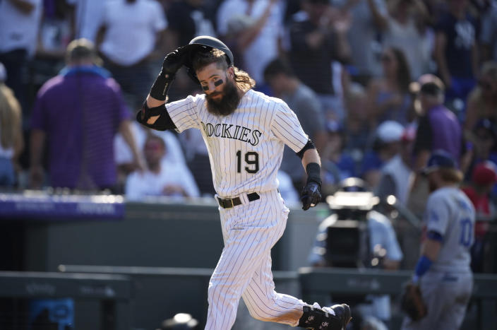 Colorado Rockies' Charlie Blackmon pulls off his helmet as he circles the bases after hitting a solo home run off Los Angeles Dodgers relief pitcher Phil Bickford during the 10th inning of a baseball game Sunday, July 18, 2021, in Denver. The Rockies won 6-5. (AP Photo/David Zalubowski)