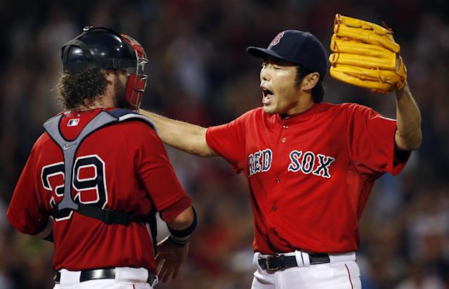 Boston Red Sox closer Koji Uehara, right, celebrates with catcher Jarrod Saltalamacchia after the last out of the ninth inning as they defeated the Chicago White Sox 4-3 in a baseball game at Fenway Park in Boston, Friday, Aug. 30, 2013. (AP Photo/Elise Amendola)