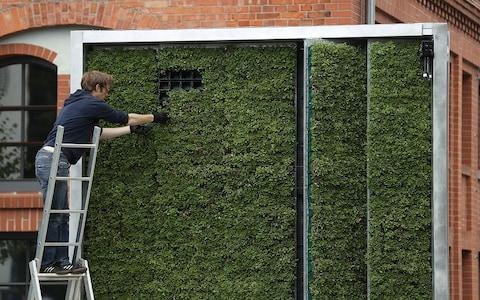 A moss-covered 'tree' is installed in Berlin - Credit: Getty