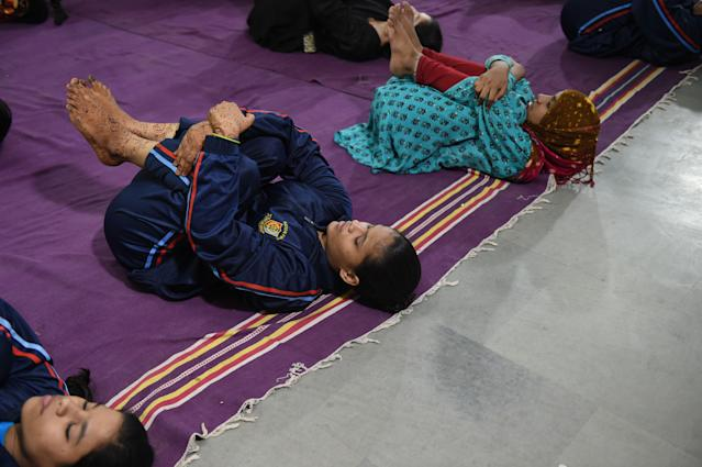 Varios niños practican yoga. (SAM PANTHAKY/AFP via Getty Images)