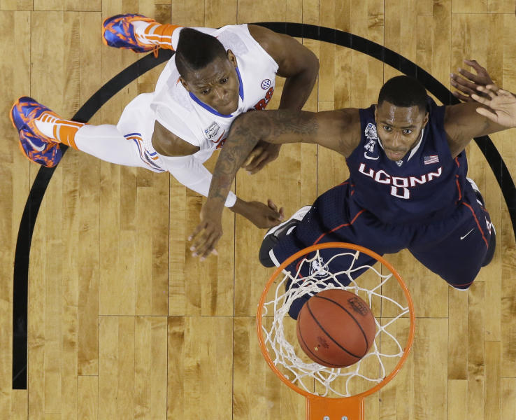 Florida forward Will Yeguete, left, and Connecticut forward Phillip Nolan, right, eye a made basket during the first half of an NCAA Final Four tournament college basketball semifinal game Saturday, April 5, 2014, in Arlington, Texas. (AP Photo/David J. Phillip)