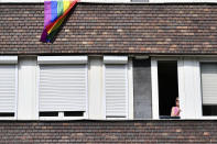 A rainbow flag hangs froma building as a woman watches participants in a gay pride parade in Budapest, Hungary, Saturday, July 24, 2021. Hungary's government led by right-wing Prime Minister Viktor Orban passed a law in June prohibiting the display of content depicting homosexuality or gender reassignment to minors, a move that has ignited intense opposition in Hungary while EU lawmakers have urged the European Commission to take swift action against Hungary unless it changes tack. (AP Photo/Anna Szilagyi)