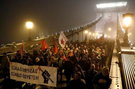 "FILE PHOTO: People march at the Chain Bridge during a protest against the new labour law in Budapest, Hungary, December 13, 2018. The banner reads ""Free Country, Free University"". REUTERS/Bernadett Szabo /File Photo"