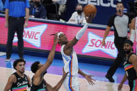 Oklahoma City Thunder guard Shai Gilgeous-Alexander shoots between San Antonio Spurs guard Tre Jones, left, forward Trey Lyles, second from left, and guard Patty Mills, right, during the second half of an NBA basketball game Wednesday, Feb. 24, 2021, in Oklahoma City. (AP Photo/Sue Ogrocki)