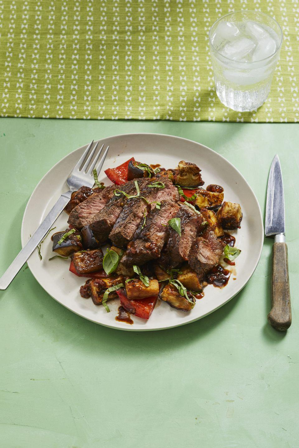 """<p>Gluten-free and filling, this dish is destined to become a new family favorite.</p><p><a href=""""https://www.womansday.com/food-recipes/food-drinks/a28354436/balsamic-steak-with-eggplant-and-peppers-recipe/"""" rel=""""nofollow noopener"""" target=""""_blank"""" data-ylk=""""slk:Get the recipe for Balsamic Steak with Eggplant and Peppers."""" class=""""link rapid-noclick-resp""""><em>Get the recipe for Balsamic Steak with Eggplant and Peppers.</em></a></p>"""