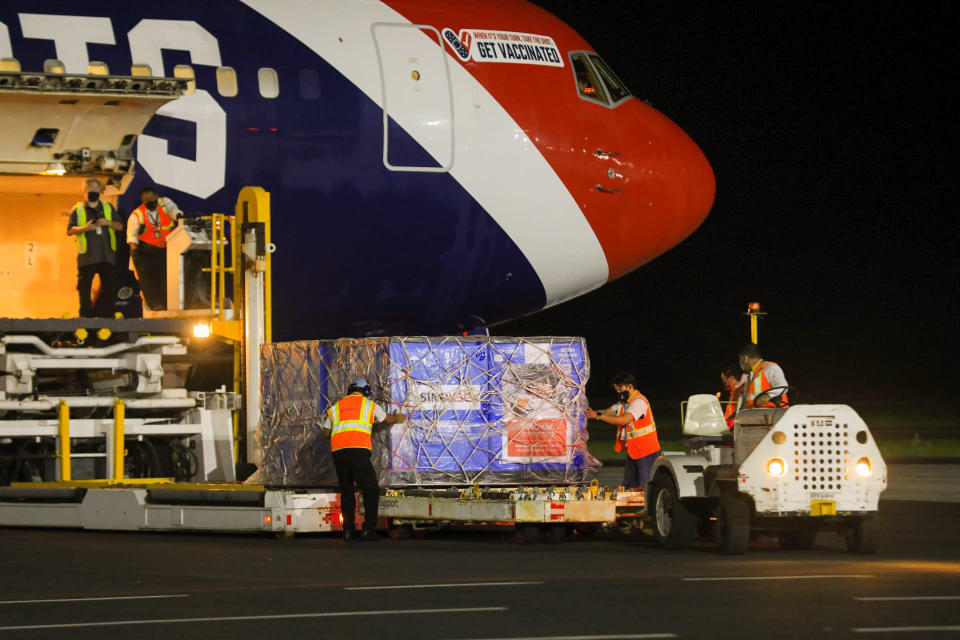 In this photo provided by El Salvador's presidential press office, airport workers unload a container of Chinese-made Sinovac COVID-19 vaccines from The New England Patriots team plane at the airport in San Salvador, El Salvador, late Tuesday, May 18, 2021. (El Salvador's presidential press office via AP)