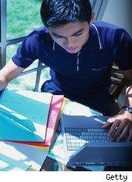 College student studying using notebooks and a computer
