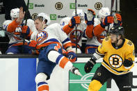 New York Islanders center Casey Cizikas, left, falls into the boards after contact with Boston Bruins right wing David Pastrnak, right, in the second period of an NHL hockey game, Thursday, April 15, 2021, in Boston. (AP Photo/Elise Amendola)