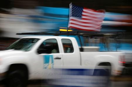 A PG&E truck carrying an American Flag drives past PG&E repair trucks in Paradise