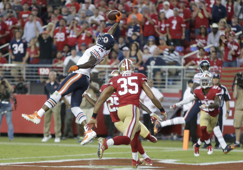 FILE - In this Sept. 14, 2014, file photo, Chicago Bears wide receiver Brandon Marshall (15) makes a one handed catch of a 17-yard touchdown pass between San Francisco 49ers safety Eric Reid (35) and strong safety Jimmie Ward (25) during the second quarter of an NFL football game in Santa Clara, Calif. The one-handed catch by New York Giants' Odell Beckham Jr. that became the most talked-about play from Sunday, Nov. 23, 2014, did more than just boost his standing with the New York Giants, it paid off a routine growing popular among many skill players of practicing the impractical, one-handed circus grab.(AP Photo/Marcio Jose Sanchez, File)