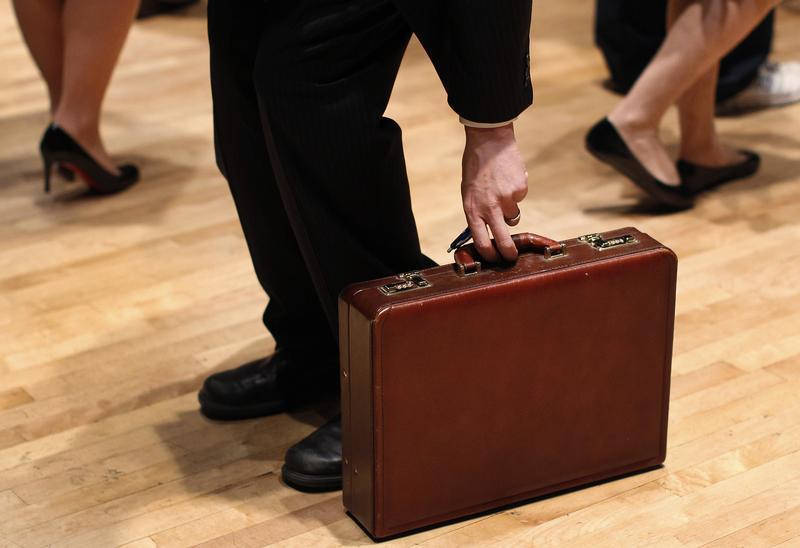 A man grabs his briefcase as he waits in line to speak with employers at the UJA-Federation Connect to Care job fair in New York