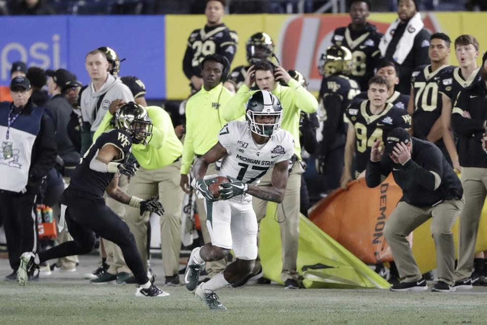 Michigan State wide receiver Tre Mosley (17) runs away from Wake Forest defensive back Amari Henderson (4) during the second half of the Pinstripe Bowl NCAA college football game Friday, Dec. 27, 2019, in New York. (AP Photo/Frank Franklin II)
