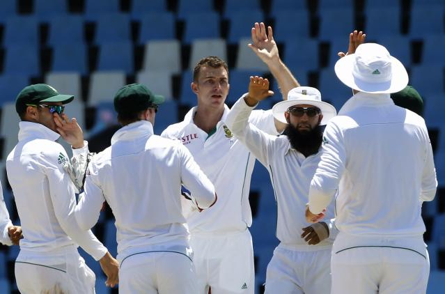South Africa's Ryan McLaren (C) celebrates with teammates the dismissal of Australia's Steve Smith after he was caught by South Africa's Robin Peterson during the second day of their cricket test in Centurion February 13, 2014. REUTERS/Siphiwe Sibeko (SOUTH AFRICA - Tags: SPORT CRICKET)