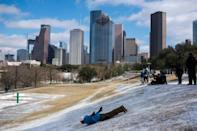 A man sleds down a snow covered hill in Houston, Texas on February 15, 2021
