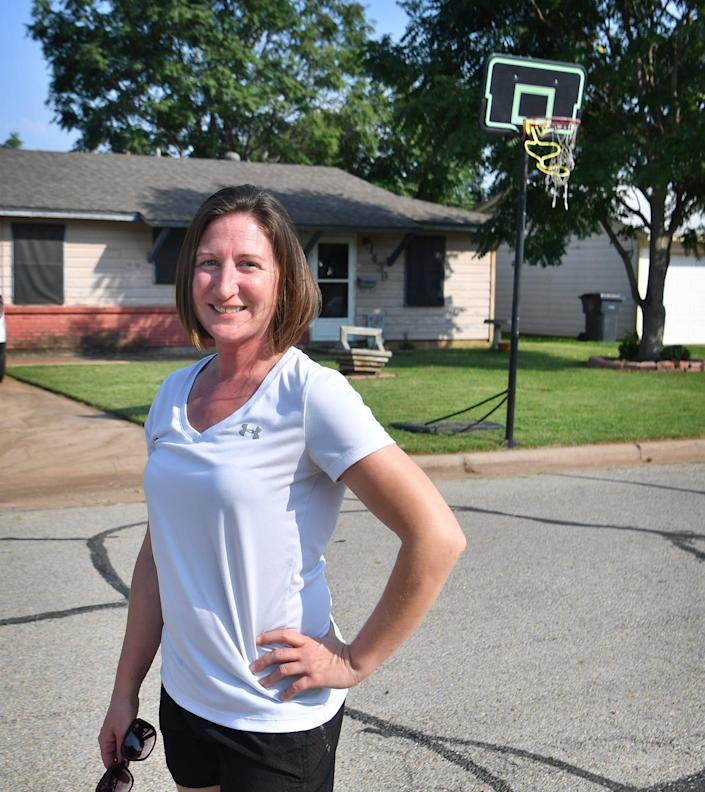 Kari Hill stands in front of house where the portable basketball goal is set up in her front yard. Hill had been issued citations for encroachment and the case was a topic of discussion during a recent City Council meeting.