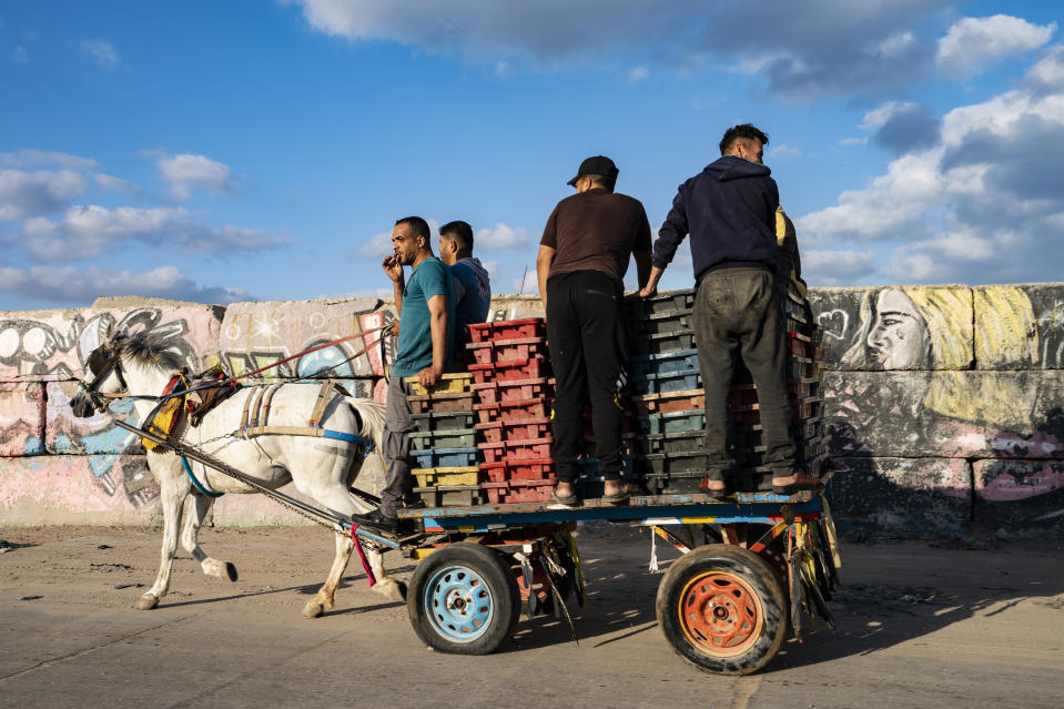 A fisherman takes a drag of a cigarette as the day's haul is delivered to market by horse-drawn cart after a limited number of boats were allowed to return to the sea following a cease-fire reached after an 11-day war between Hamas and Israel, in Gaza City, Sunday, May 23, 2021. (AP Photo/John Minchillo)