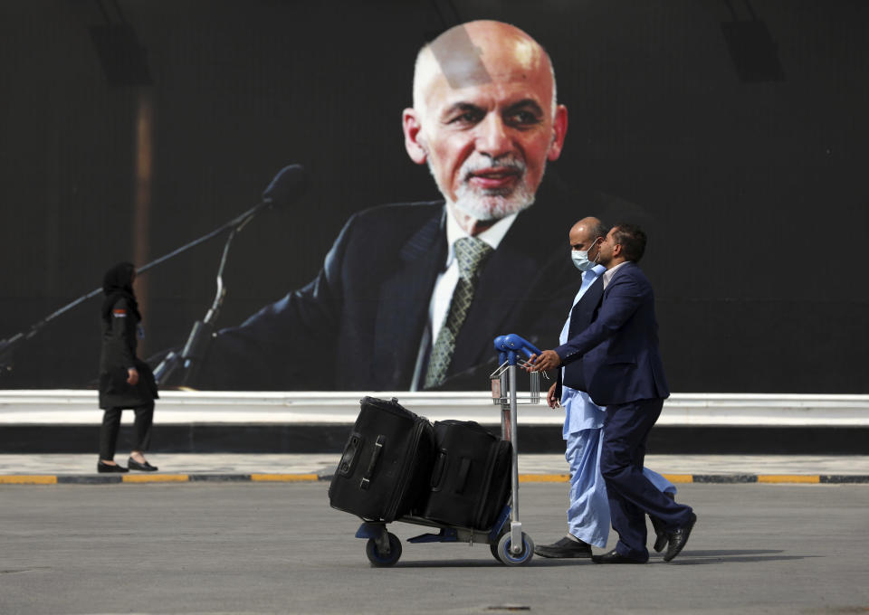 Passengers walk to the departures terminal of Hamid Karzai International Airport in Kabul, Afghanistan, on Saturday, Aug. 14, 2021, past a mural of President Ashraf Ghani, as the Taliban offensive encircled the capital. (AP Photo/Rahmat Gul)
