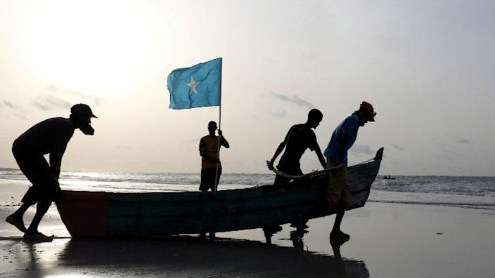 Fishermen carry a boat in to the water on Lido Beach, Mogadishu, Somalia - Friday 18 June 2021