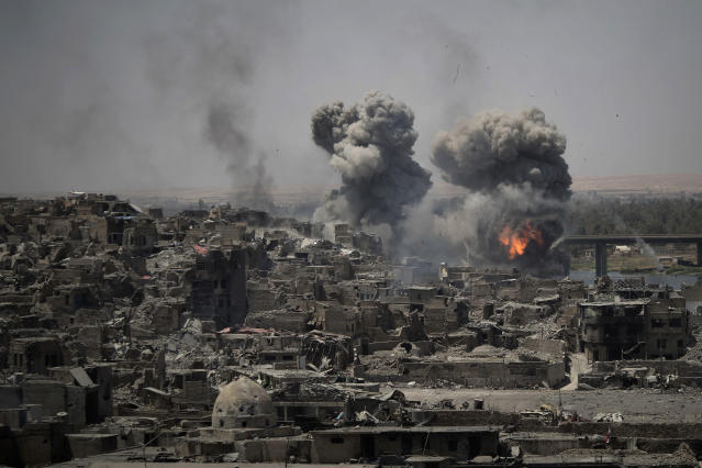 """FILE - In this July 11, 2017, file photo, airstrikes target Islamic State positions on the edge of the Old City a day after Iraq's prime minister declared """"total victory"""" in Mosul, Iraq. (AP Photo/Felipe Dana, File)"""