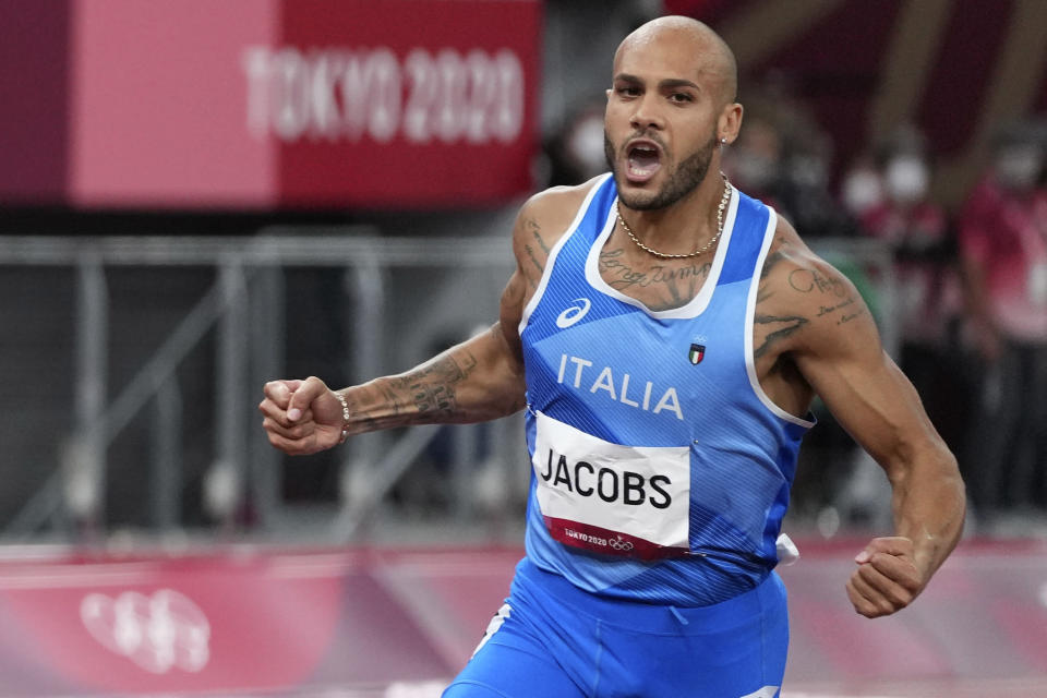 Lamont Jacobs of Italy crosses the finish line to win the men's the 100-meter final at the 2020 Summer Olympics, Sunday, Aug. 1, 2021, in Tokyo. (AP Photo/Matthias Schrader)