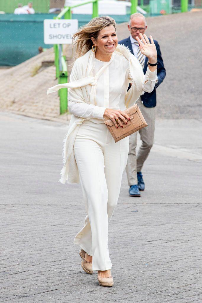 <p>Queen Maxima of the Netherlands knows how to make even nude espadrilles and an all-white outfit look luxurious. A scarf, blood red nail polish, and chunky hoop earrings? Perfection. </p>