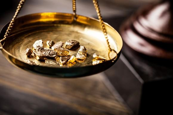 Tiny fragments of gold sitting on an old-fashioned scale.