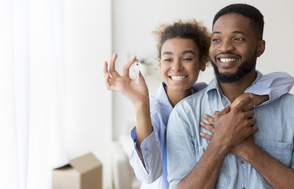 Joyful African American Couple Holding Key Embracing Standing In New Flat After Moving. Selective Focus, Copy Space