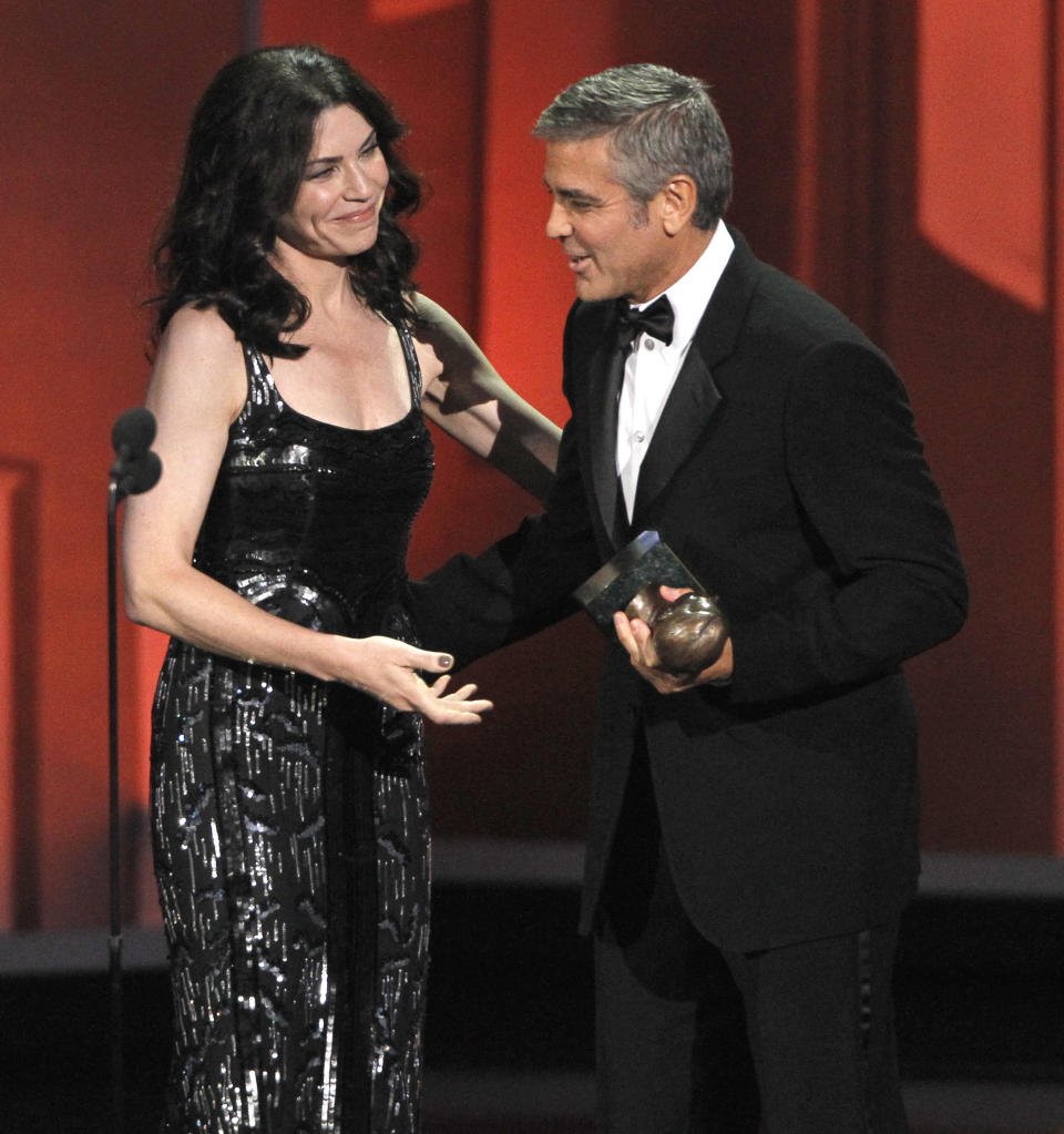 George Clooney, right, accepts the Bob Hope Humanitarian Award from presenter Julianna Margulies during the 62nd Primetime Emmy Awards Sunday, Aug. 29, 2010, in Los Angeles. (AP Photo/Chris Carlson)