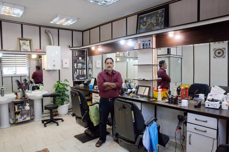 An Iranian barber in his empty barbershop in Tehran, complaining that some days he has no customers because people prefer to spend only on essential services (EPA)