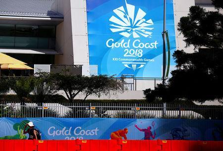 FILE PHOTO: A pedestrian walks past a security fence and barricades located outside a venue for the upcoming Commonwealth Games on the Gold Coast in Australia, April 3, 2018. REUTERS/David Gray/File Photo