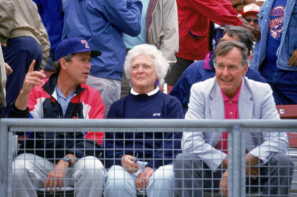 Co-owner and managing general partner of the Texas Rangers George W. Bush (left) sits with his fatherand mother, as they attend a Texas Rangers game in Arlington, Texas, in the 1990s.