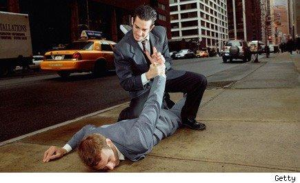 man in suit twisting the other arm of another man in the suit who is on the ground