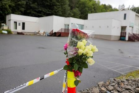 Flowers and a police tape are seem outside Al-Noor Islamic Centre Mosque, a day after a gunman's attack, in Baerum outside Oslo