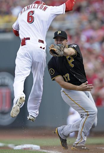 Cincinnati Reds' Billy Hamilton (6) jumps in the air to avoid a tag by Pittsburgh Pirates first baseman Gaby Sanchez (17) in the first inning of a baseball game, Friday, July 11, 2014, in Cincinnati. Hamilton was safe at first. (AP Photo/Al Behrman)