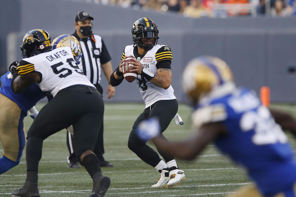 Hamilton Tiger-Cats quarterback Jeremiah Masoli (8) drops back during the first half of a Canadian Football League game against the Winnipeg Blue Bombers on Thursday, Aug. 5, 2021, in Winnipeg, Manitoba. (John Woods/The Canadian Press via AP)