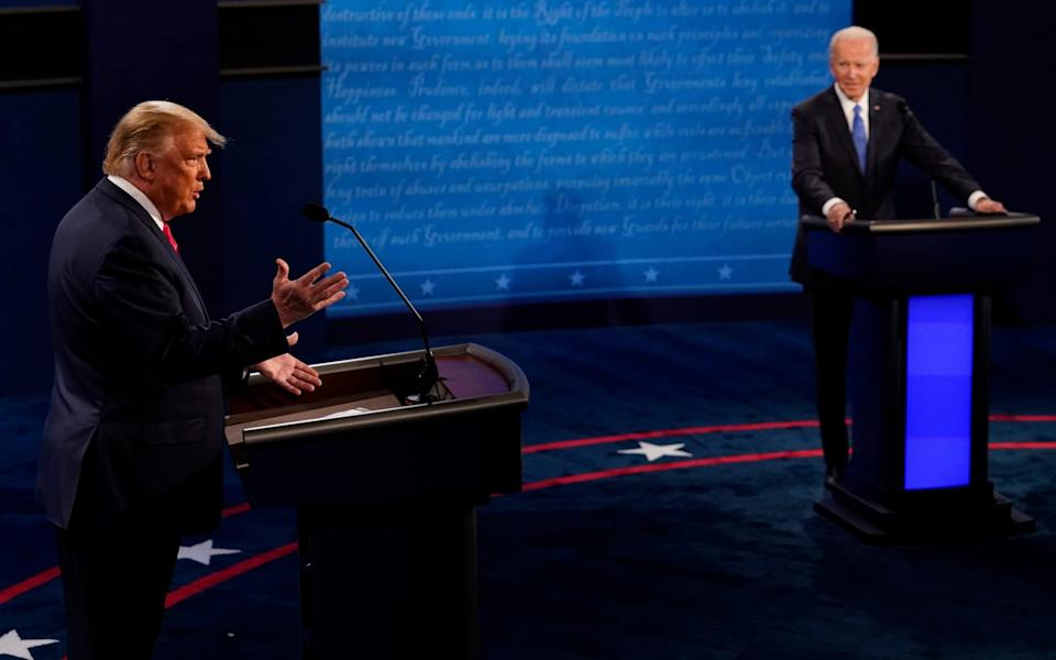 President Donald Trump answers a question as Democratic presidential candidate former Vice President Joe Biden listens during the second and final presidential debate Thursday, Oct. 22, 2020, at Belmont University in Nashville, Tenn - AP