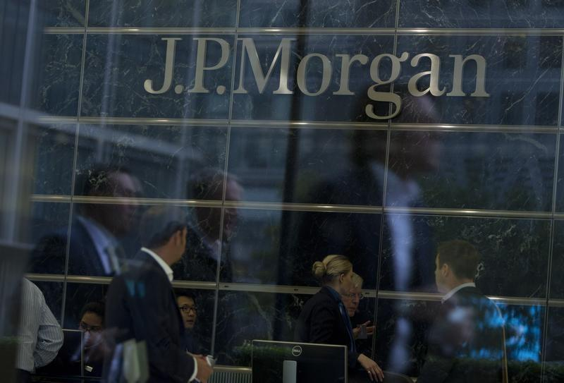 Workers are reflected in the windows of the Canary Wharf offices of JP Morgan in London