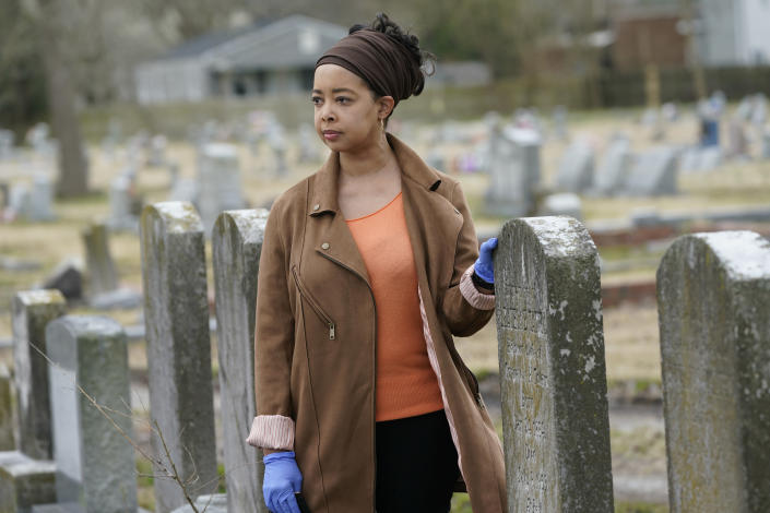 Nadia Orton, a genealogist and family historian in Virginia, poses next to tombstones at the Lincoln Memorial Cemetery in Portsmouth, Va., Tuesday, March 23, 2021. Orton has worked tracing her own family and others to historically Black cemeteries. (AP Photo/Steve Helber)
