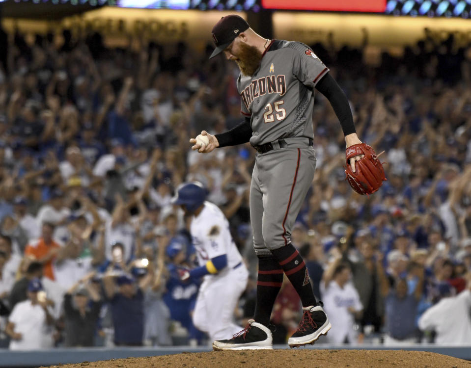 Arizona Diamondbacks pitcher Archie Bradley looks down after giving up a three-run home run to Los Angeles Dodgers' Matt Kemp, rounding the bases, in the eighth inning of a baseball game, Saturday, Sept. 1, 2018, in Los Angeles. (AP Photo/Michael Owen Baker)