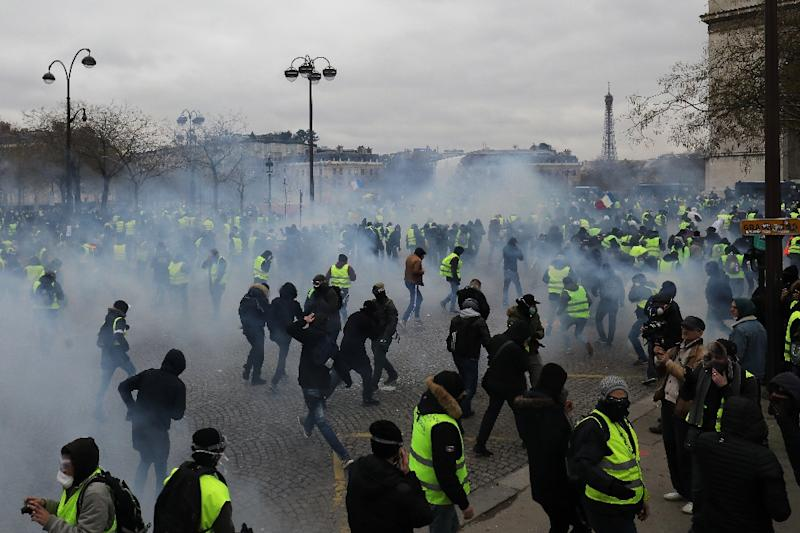 "Police fired tear gas and water cannon to disperse advancing ""yellow vest"" protesters at the Arc de Triomphe in Paris on Saturday (AFP Photo/LUDOVIC MARIN)"