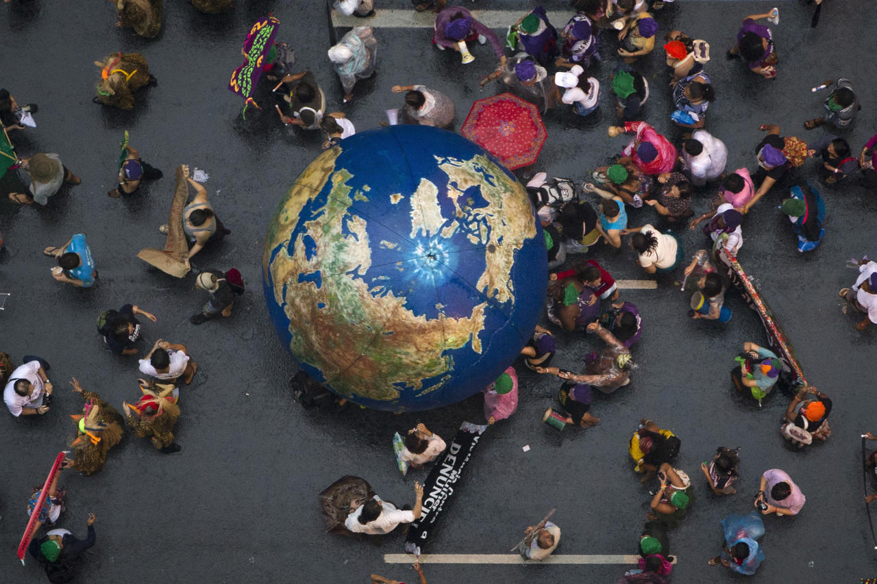 """Activists push an inflatable globe during a """"Global March"""" as part of the People's Summit for Social and Environmental Justice in Defense of the Commons, a parallel event during the UN Conference on Sustainable Development, or Rio+20, in Rio de Janeiro, Brazil, Wednesday, June 20, 2012. (AP Photo/Felipe Dana)"""