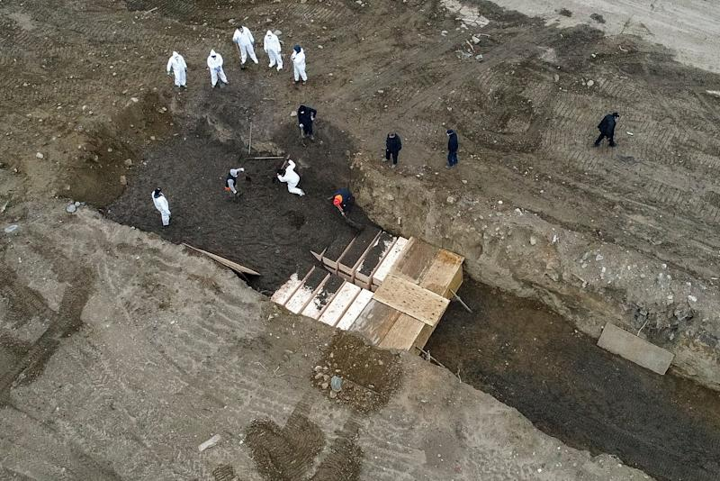 Workers wearing personal protective equipment bury bodies in a trench on Hart Island, Thursday, April 9, 2020, in the Bronx borough of New York. On Thursday, New York City's medical examiner confirmed that the city has shortened the amount of time it will hold on to remains to 14 days from 30 days before they will be transferred for temporary internment at a City Cemetery. Earlier in the week, Mayor Bill DeBlasio said that officials have explored the possibility of temporary burials on Hart Island, a strip of land in Long Island Sound that has long served as the city's potter's field. (AP Photo/John Minchillo) ORG XMIT: NYJM114
