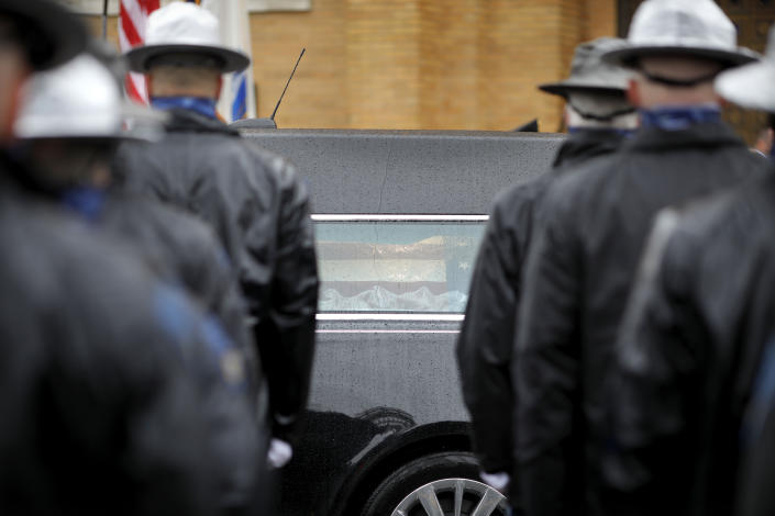 """Law enforcement personnel line the streets as the hearse carrying the casket of Capitol Police Officer William """"Billy"""" Evans arrives at St. Stanislaus Kotska Church for his funeral on Thursday, April 15, 2021, in Adams, Mass. Evans was killed this month when a driver struck him and another officer at a barricade outside the Senate. (Stephanie Zollshan/The Berkshire Eagle via AP)"""