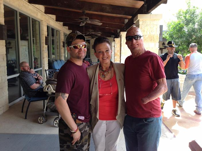 Maggie Lockridge poses with two veterans. Her foundation, Rebuilding America's Warriors, pairs wounded vets with plastic surgeons to repair their injuries in the most aesthetically pleasing way. (Photo: Courtesy of Rebuilding America's Warriors)