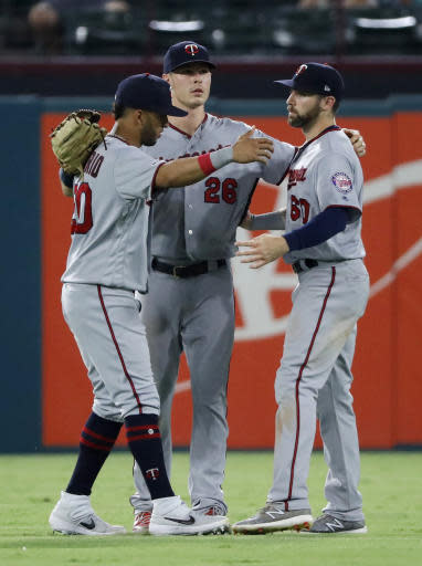 Minnesota Twins' Eddie Rosario, Max Kepler (26) and Jake Cave, right, celebrate the team's 13-6 win over the Texas Rangers in a baseball game in Arlington, Texas, Thursday, Aug. 15, 2019. (AP Photo/Tony Gutierrez)
