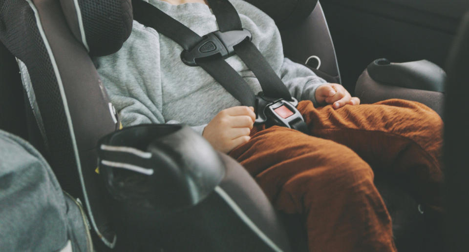 Little boy sitting in car on child's seat with fastened seat belt.