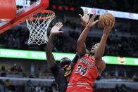 Chicago Bulls' Wendell Carter Jr. (34) goes up for a shot against Cleveland Cavaliers' Andre Drummond (3) during the second half of an NBA basketball game Tuesday, March 10, 2020, in Chicago. (AP Photo/Paul Beaty)